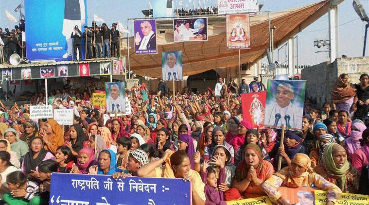 Followers shield the Satlok Ashram of Sant Rampal in Hisar on Monday to resist his arrest. (Source: PTI)