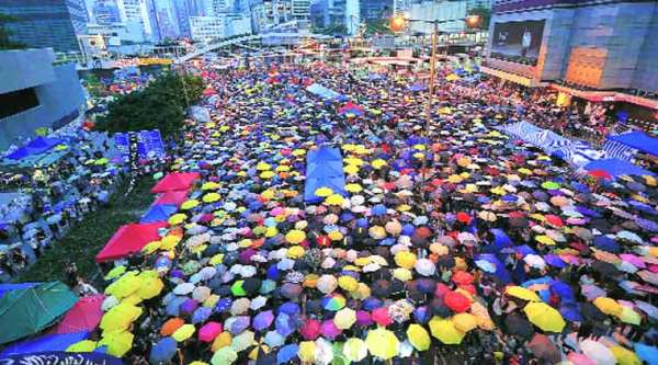 Protesters open their umbrellas, symbols of pro-democracy movement, as they mark one month since they took to the streets in Hong Kong's financial central district .