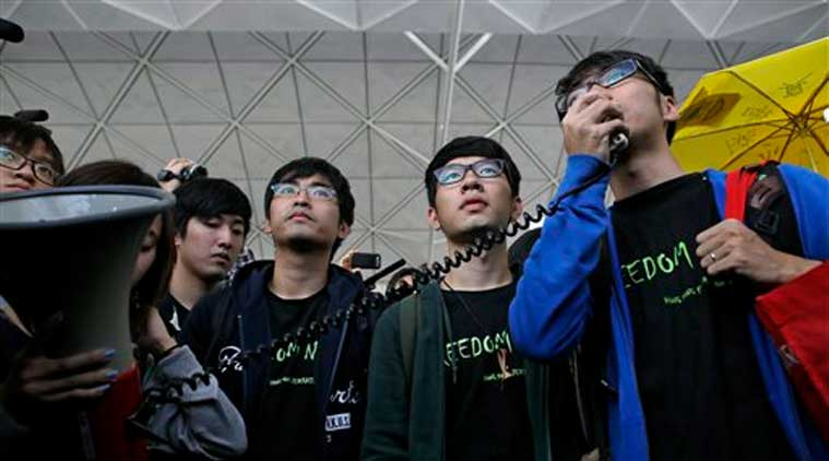 Hong Kong Federation of Students leader Alex Chow, left, committee members Nathan Law, center, and Eason Chung speak to supporters before attempting to travel to Beijing, at Hong Kong International Airport Saturday, Nov. 15, 2014. Three students who have led protests for greater democracy in Hong Kong were denied permission to travel to Beijing to meet with China's top officials. (Source: AP)