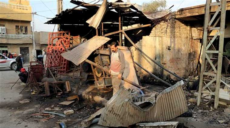 A civilian inspects the site of Friday's car bomb in Baghdad's Gorayaat neighborhood, Iraq, Saturday (Source: AP)