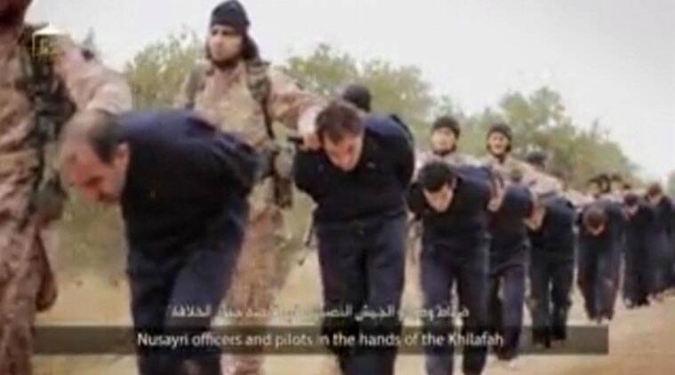 This still image taken from an undated video published on the Internet by the Islamic State group militants and made available, Sunday, Nov. 16, 2014, purports to show extremists marching Syrian soldiers before beheading them. The high-definition video later shows the beheadings of about a dozen men identified as Syrian military officers and pilots, all dressed in blue jumpsuits. The Associated Press could not independently verify the footage, though it appeared on websites used in the past by the Islamic State group, which now controls a third of Syria and Iraq. (Source: AP Photo)