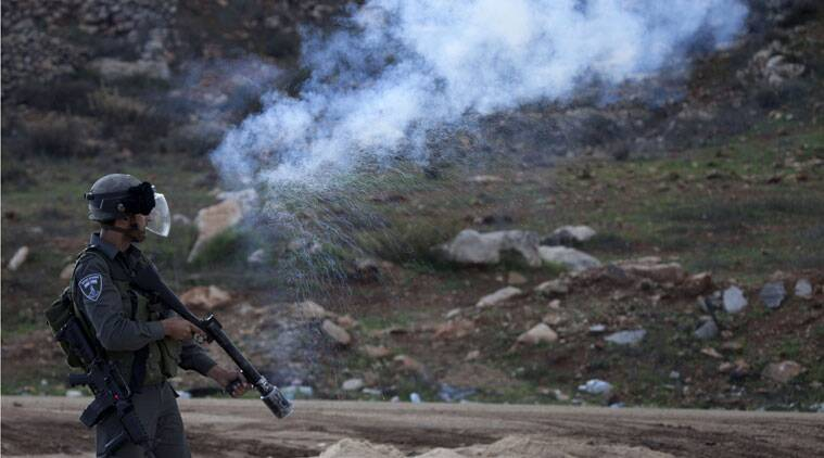 An Israeli border policeman fires a tear gas canister during clashes with Palestinian protesters, outside the Ofer military prison, near the West Bank city of Ramallah, Tuesday, Nov. 18, 2014. Two Palestinian cousins armed with meat cleavers and a gun stormed a Jerusalem synagogue during morning prayers Tuesday, killing four people in the city's bloodiest attack in years. The attack ratcheted up fears of sustained violence in a city already on edge amid soaring tensions over its most contested holy site. (Source: AP)