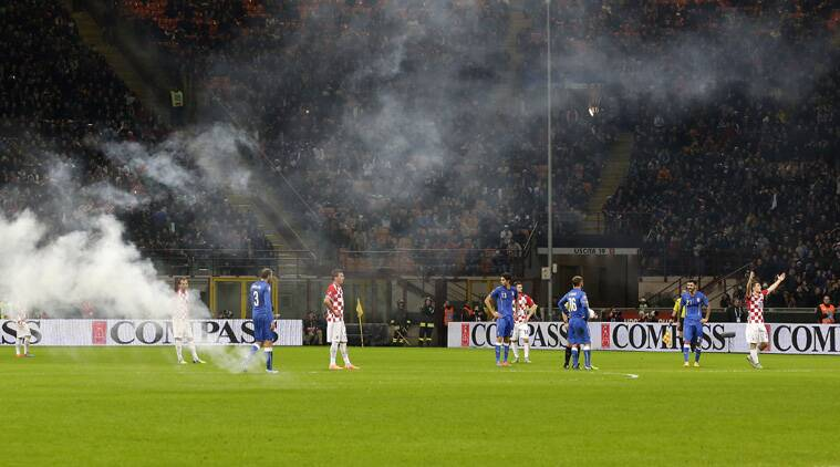 Players stand on the field of play as Croatia supporters throw flares during the Euro 2016 qualifying soccer match between Italy and Croatia (Source: AP)