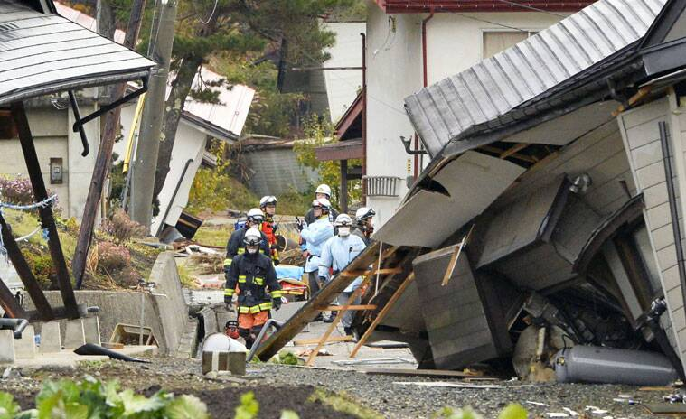 Firefighters and rescuers examine buildings collapsed after a strong earthquake hit Hakuba, Nagano prefecture, central Japan, Sunday, Nov. 23, 2014. The magnitude-6.8 earthquake shook on Saturday night the mountainous area that hosted the 1998 Winter Olympics destroying more than half a dozen homes in the ski resort town and injuring at least 30 people, officials said. (Source: AP Photo/Kyodo News)