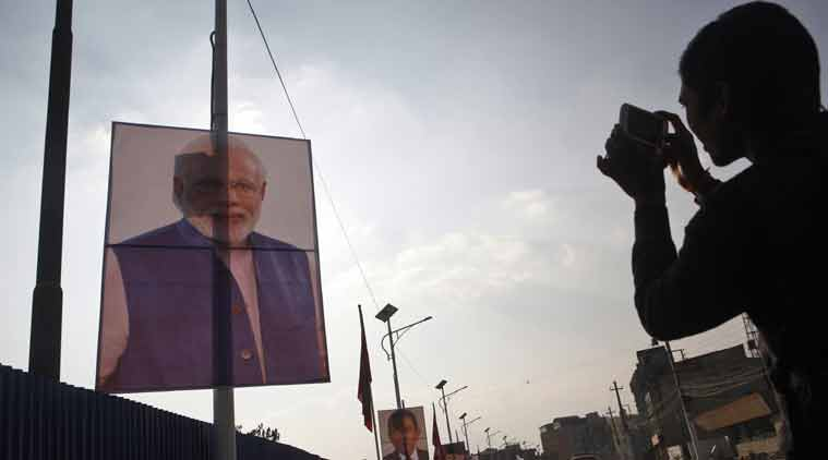 A Nepalese man photographs a portrait of Indian Prime Minister Narendra Modi displayed on a road side along with other heads of South Asian Association for Regional Cooperation (SAARC), countries in Katmandu, Nepal (Source: AP)