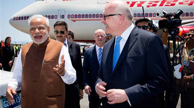 PM Narendra Modi walks with Australia's Attorney-General George Brandis on his arrival at Brisbane Airport ahead of the G-20 summit in Brisbane, Australia on Friday. (Source: AP photo)