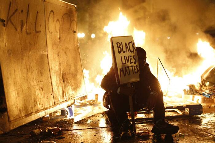 A demonstrator sits in front of a street fire during a demonstration following the grand jury decision in the Ferguson, Missouri shooting of Michael Brown, in Oakland, California November 25, 2014. The grand jury decided on Monday not to indict a white police officer over the fatal August shooting of an unarmed black teenager. (Source: Reuters)