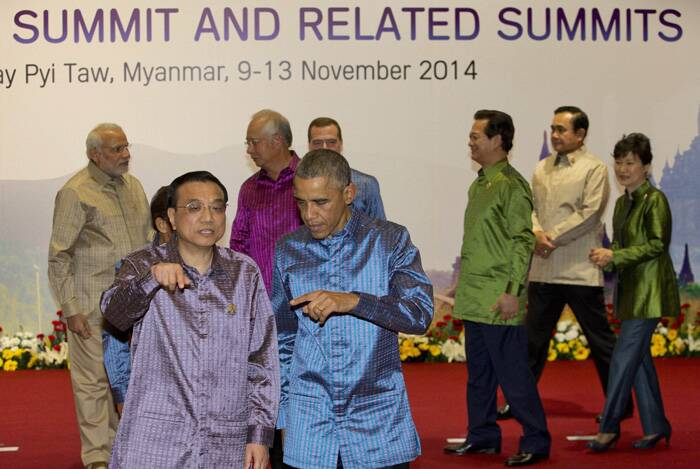 Prime Minister Narendra Modi (L) seen at the back as US President Barack Obama and Chinese Prime Minister Li Keqiang gesture as they walk after posing for a group photo with leaders of Association of Southeast Asian Nations  (ASEAN) and related summits ahead of a gala dinner at Myanmar International Convention Center in Naypyitaw, Myanmar on Wednesday. (Source:  PTI)