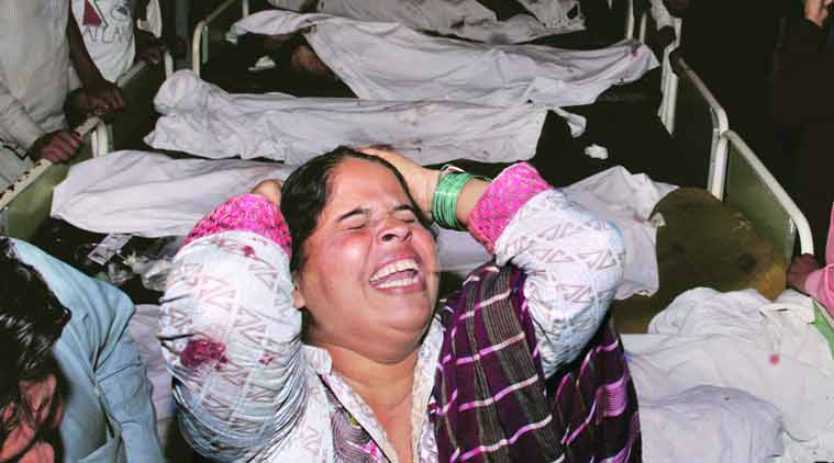 A woman grieves next to the bodies of victims of the Wagah bomb blast, at a Lahore hospital on Sunday. (Source: AP photo)