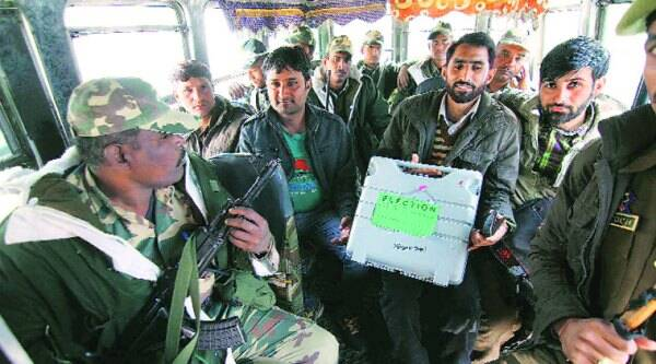 Under armed guard, poll personnel carry EVMs to voting centres in Doda, Chenab valley, on Monday. (Source: IE photo  by Mir Imran)