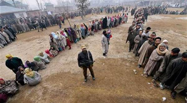 A security person stands guard as people wait in queues to cast their votes for Assembly elections at a polling station in Bandipora district of Jammu and Kashmir on Tuesday. (PTI Photo)