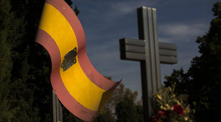 Flowers are placed on the tomb of Spanish Army Blue Division members who died during WWII, next a Spanish pre-constitutional flag during All Saints Day, a Catholic holiday to reflect on the saints and deceased relatives, Madrid, Spain.
