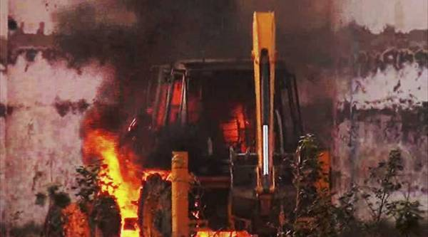 A JCB machine burns during violent clash between Police and Sant Rampal's followers at Satlok Ashram in Hisar on Tuesday. Supporters of Rampal indulged in clashes with the police to resist his arrest. (PTI Photo)