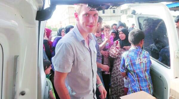 This undated photo shows Peter Kassig delivering supplies for Syrian refugees. (Source: AP)