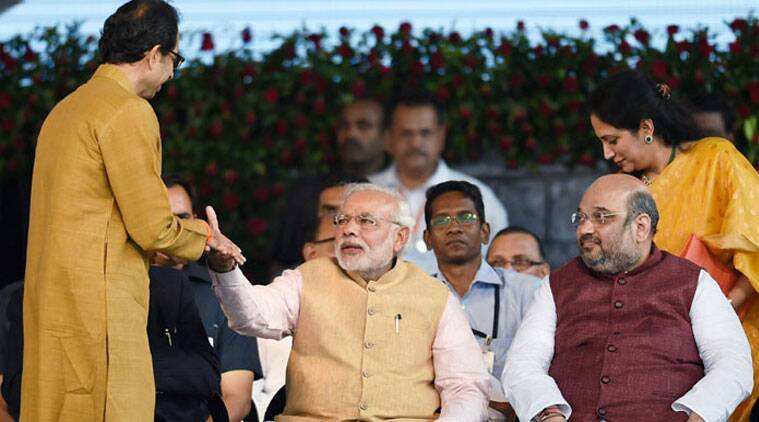 PM Narendra Modi shakes hands with Shiv Sena chief Uddhav Thackeray as BJP President Amit Shah looks on during the swearing-in ceremony of new Maharashtra government in Mumbai on Friday. (Source: PTI)