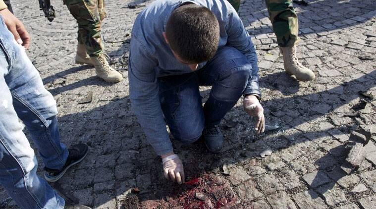 An investigator works at the site of a suicide attack in Irbil, capital of the semi-autonomous Kurdish region in northern Iraq that took place near the city's historic citadel on Wednesday, Nov. 19, 2014. The bomber struck in the heart of the northern Iraqi Kurdish city, killing several people, according to initial reports in local Kurdish media.(Source: AP)