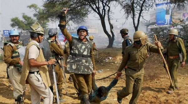 Security personnel drag away a follower of Sant Rampal during a clash outside Satlok Ashram in Hisar. Supporters of Rampal indulged in clashes with the police to resist his arrest. (Source: PTI Photo)