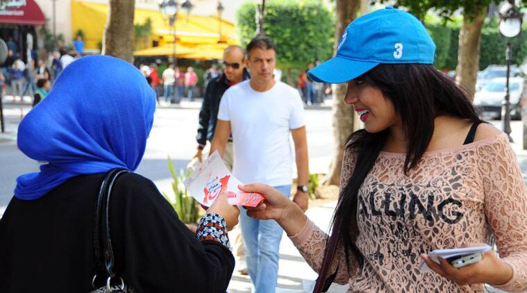 An electoral volunteer, right, distributes leaflets, Friday, Oct. 24, 2014, to encourage the public to vote on the iconic Bourguiba Avenue which witnessed the culmination of Tunisia's revolution against dictator Zine El Abidine Ben Ali in 2011, in Tunis, Tunisia. Tunisians will flock to the polls on Sunday, Oct. 26, 2014, to elect representatives for a four year parliament in one of the final steps for the country's transition to democracy after overthrowing its leader more than three years ago. (Source: AP)