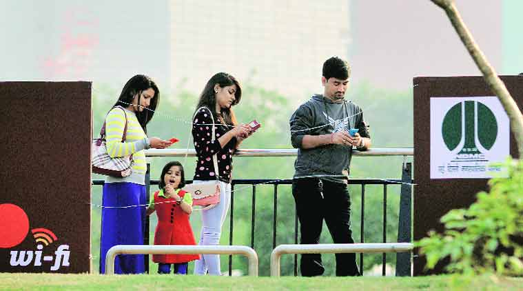 Visitors enjoying public Wi-Fi service at Connaught Place, New Delhi on Sunday. (Source: Express photo by Ravi Kanojia)