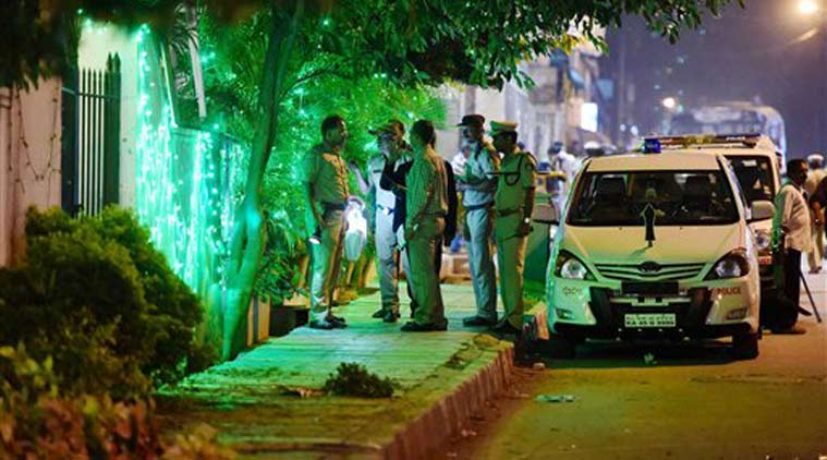 Police officials on spot where a low intensity bomb blast occurred at church street in Bengaluru on Sunday night. (Source photo: PTI )