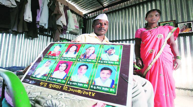 Lehmbe shows photographs of his wife and seven children who died in the landslide. Lehmbe's newly-wedded wife Maneesha stands near him at his temporary shed in Malin village. (Source photo by Arul Horizon)