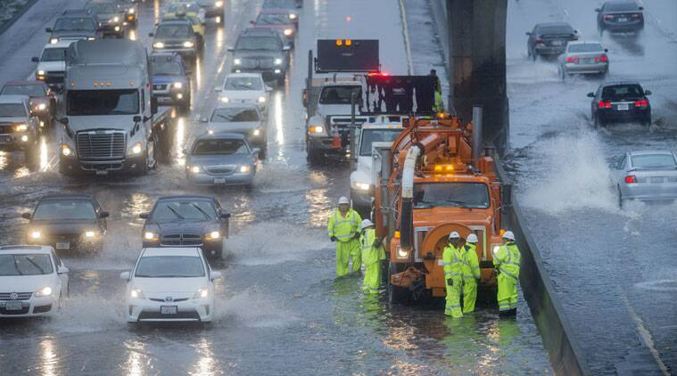 A Caltrans crew tries to clear a flooded stretch of Highway 101 in South San Francisco, California. (Source: AP photo)