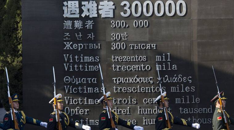"Chinese honor guard members march past the words ""Victims 300000"" during a ceremony to mark China's first National Memorial Day at the Nanjing Massacre Memorial Hall in Nanjing in China on Saturday. (Source: AP photo)"