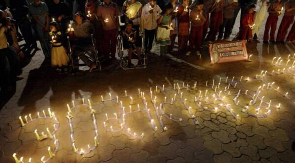 Victims of the Bhopal Gas Tragedy take part in a candle lit vigil to mark the 30th anniversary of the tragedy in Bhopal on Sunday. (Source: PTI Photo)