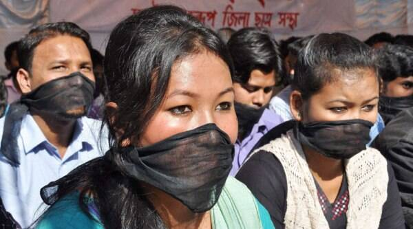 Activists of the All Assam Students Union (AASU) tie their mouths with Black clothes during a sit in protest against the brutal killing of innocent people by NDFB (S) militants, in Guwahati on Wednesday. (Source: PTI Photo)