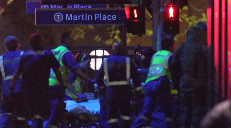 Armed tactical response officers and emergency workers attend the scene after a cafe siege in the central business district of Sydney. (Source: AP)