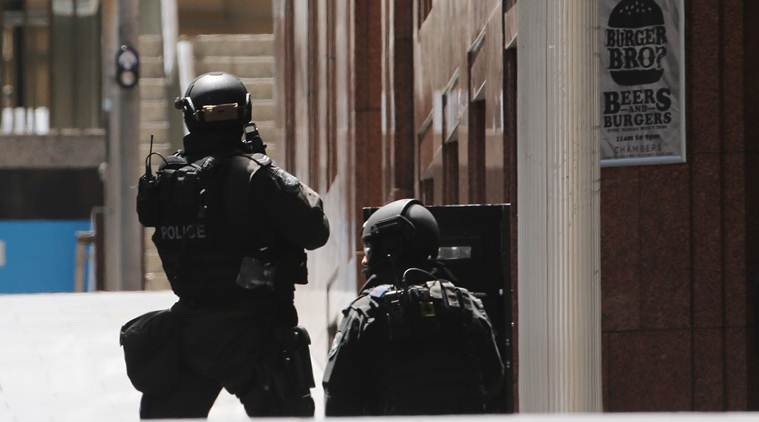Police stand at the ready close to a cafe under siege in Martin Place in the central business district of Sydney. (Source: AP)