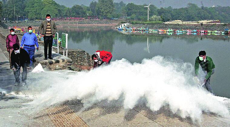Workers of Municipal Corporation throw lime around the Sukhna Lake in Chandigarh on Friday. (Source photo by Sumit Malhotra)