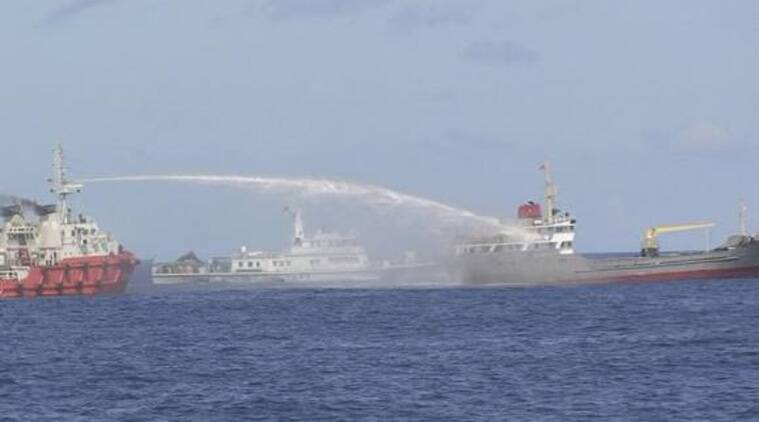 A Chinese ship (L) uses water cannon on a Vietnamese Sea Guard ship on the South China Sea near the Paracels islands, in this handout photo taken on May 3, 2014