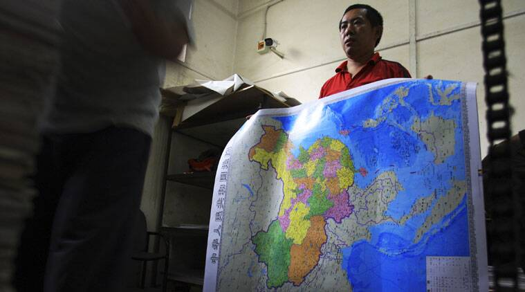 In this June 27, 2014 photo, a worker holds a new officially approved map of China that includes the islands and maritime area that Beijing claims in the South China Sea, at a printing factory in Changsha in south China's Hunan province. China has again rejected an attempt by the Philippines to challenge its territorial claims over the South China Sea through international arbitration, releasing a lengthy paper a week before the Dec. 15, 2014 deadline for China to respond to the case. China prefers to settle its disputes with discussions with the countries directly involved. But the Philippines has filed a case with an international tribunal. (AP Photo)