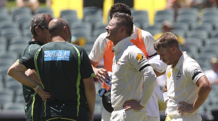Australia's Michael Clarke, second from right, in pain after injuring himself, during the first day (Source: AP)
