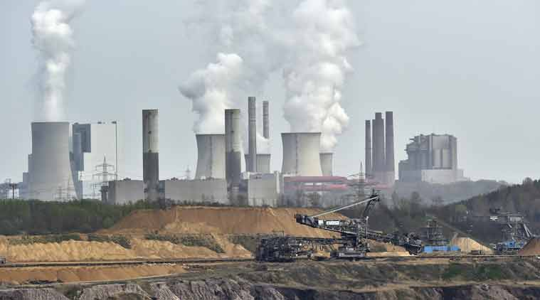 ILE - In this April 3, 2014 file photo, machines dig for brown coal at the open-cast mining Garzweiler in front of a power plant emitting steam near the city of Grevenbroich in western Germany. (Source: AP)