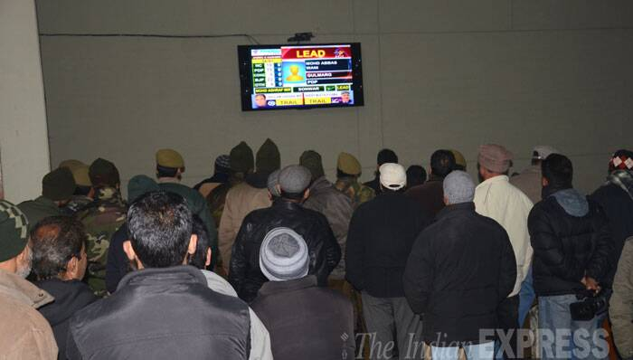 People checking the election  results live in Srinagar at a polling booth. (Source: Express photo by Shuaib Masoodi)