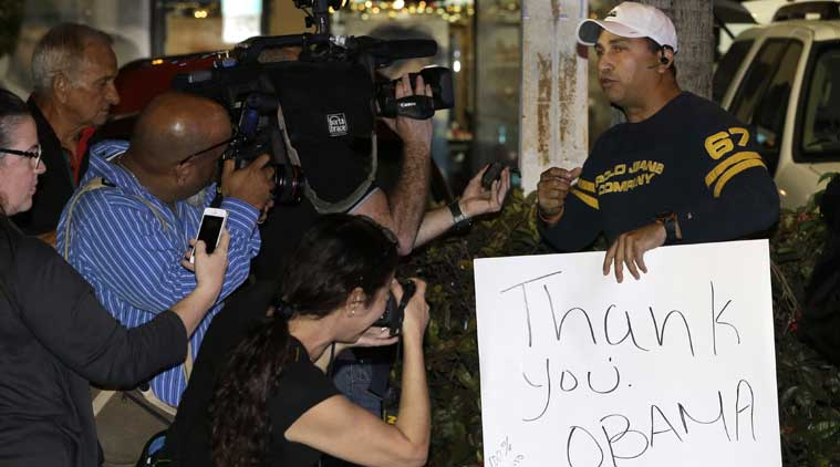 A supporter of President Obama, Abel Dominguez, left, holds a sign as he is photographed by news photographers in Miami. Dominguez said he was thankful for the announcement by the Obama administration that could pave way for a major shift in U.S. policy toward Cuba. (Source: AP )