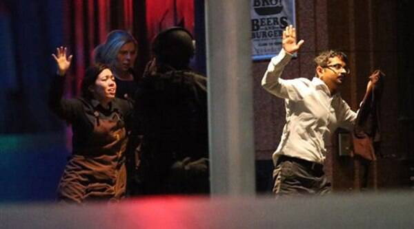 Hostages run to safety during a cafe siege in the central business district of Sydney , Australia.