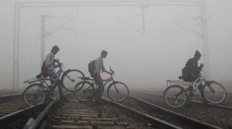 School students cross railway tracks during a cold and foggy morning in Allahabad on Friday. (Source: PTI photo)