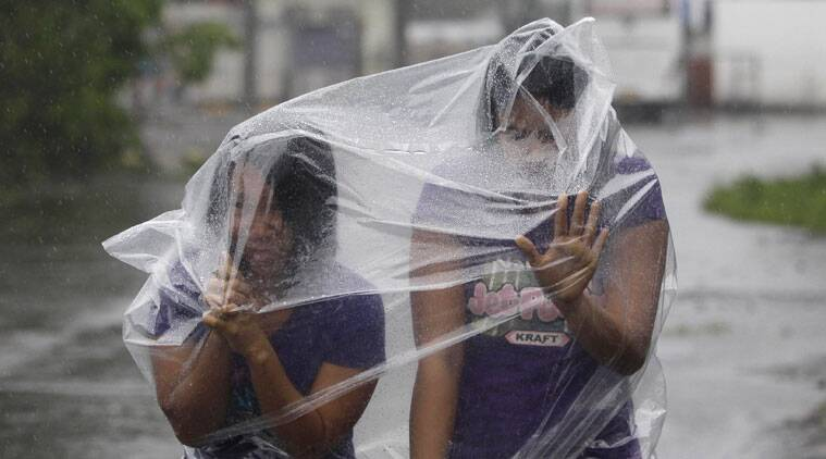 Filipino residents use plastic sheets to protect them from rains and strong winds brought by Typhoon Hagupit in Legazpi, Albay province, eastern Philippines on Sunday, Dec. 7, 2014. Typhoon Hagupit slammed into the central Philippines' east coast late Saturday, knocking out power and toppling trees in a region where 650,000 people have fled to safety, still haunted by the massive death and destruction wrought by a monster storm last year. (AP Photo/Aaron Favila)