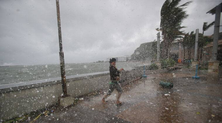A man reacts as the strong winds and rain from Typhoon Hagupit hit shore in Legazpi, Albay province, eastern Philippines on Sunday. (Source: AP)