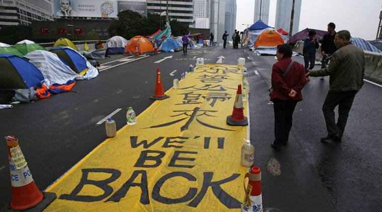 "A yellow banner reading ""We'll be back"" is displayed by protesters at the occupied area outside government headquarters in Hong Kong. (Source: AP Photo)"