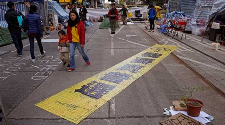 """The yellow banner reads """" I want genuine universal suffrage."""" is displayed by protesters in the Causeway Bay shopping district, one of the occupied areas in Hong Kong Saturday, Dec.13, 2014. (Source:AP)"""