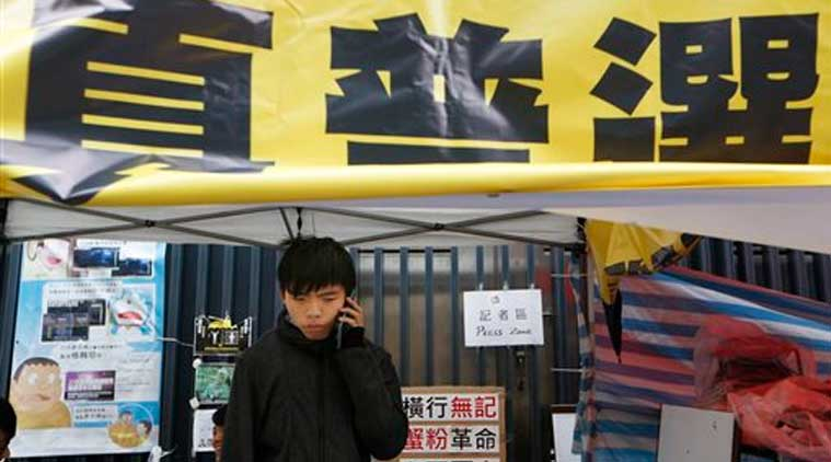 Student leader Joshua Wong talks on his phone during his hunger strike at the occupied area outside government headquarters in Hong Kong Tuesday, Dec. 2, 2014. (Source: AP)