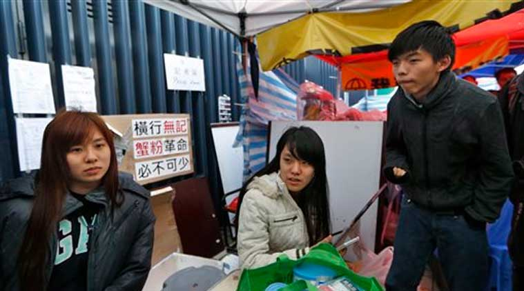 Three students, from right, Joshua Wong, Prince Wong and Isabella Lo talk to the media during their hunger strike next to their tent at the occupied area outside government headquarters in Hong Kong Tuesday, Dec. 2, 2014. (Source: AP)
