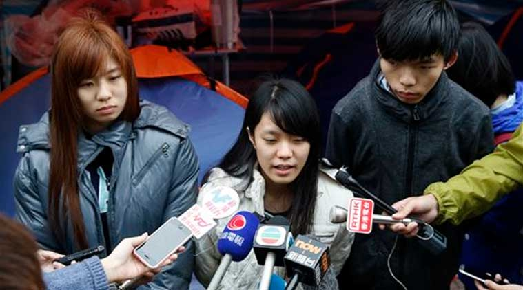 Three students, from right, Joshua Wong, Prince Wong and Isabella Lo speak to the media during their hunger strike at the occupied area outside government headquarters in Hong Kong Tuesday, Dec. 2, 2014. (Source: AP)
