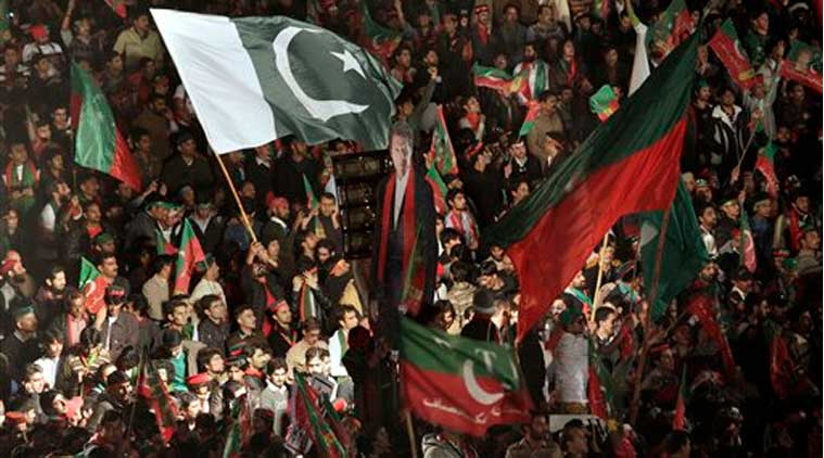 This Nov. 30, 2014 shows supporters of Pakistani politician Imran Khan wave a huge National flag as they take part in an anti-government rally in Islamabad. (Source: AP)