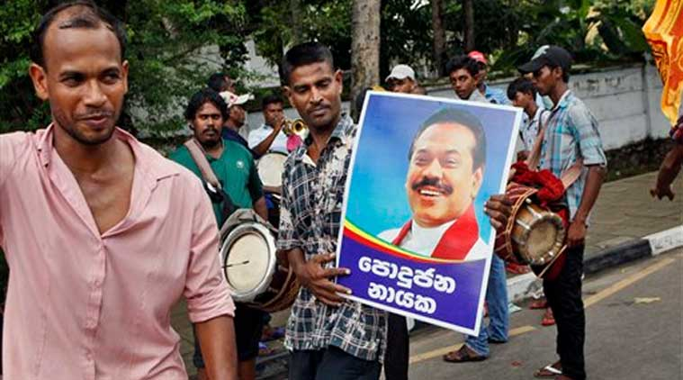 Supporters of Sri Lankan President Mahinda Rajapaksa dance carrying his portrait outside the elections office in Colombo, Sri Lanka, Monday, Dec. 8, 2014. (Source: AP)