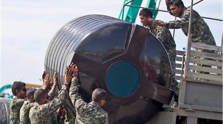 Maldivian security personnel load a water tank onto a military vehicle to fill it with treated water in Male', Maldives, Friday, Dec. 5, 2014. Water was cut off to more than 100,000 residents in the Maldives' capital because of a fire in the city's water treatment plant, and the government has declared a crisis situation, a government minister said. (Sources:AP)